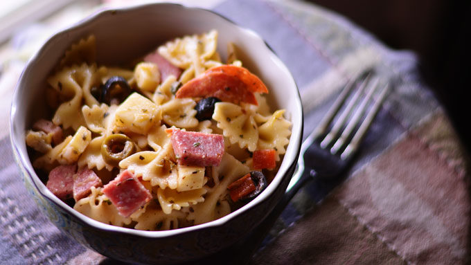 How to make delicious and hearty Muffuletta Pasta Salad, inspired by the classic Italian sandwich. Get the recipe from Cosmopolitan Cornbread
