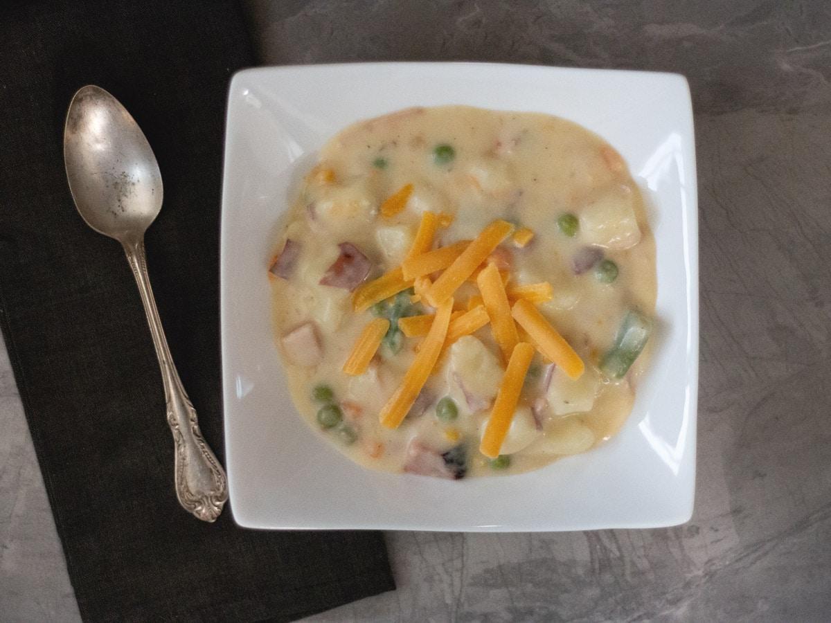 Cheddar Ham Chowder is a thick, creamy soup filled will veggies, potato and ham. Recipe from Cosmopolitan Cornbread.