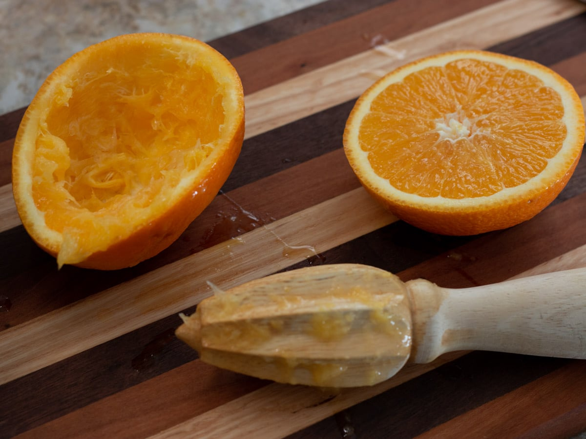 orange pieces on a cutting board with juicer