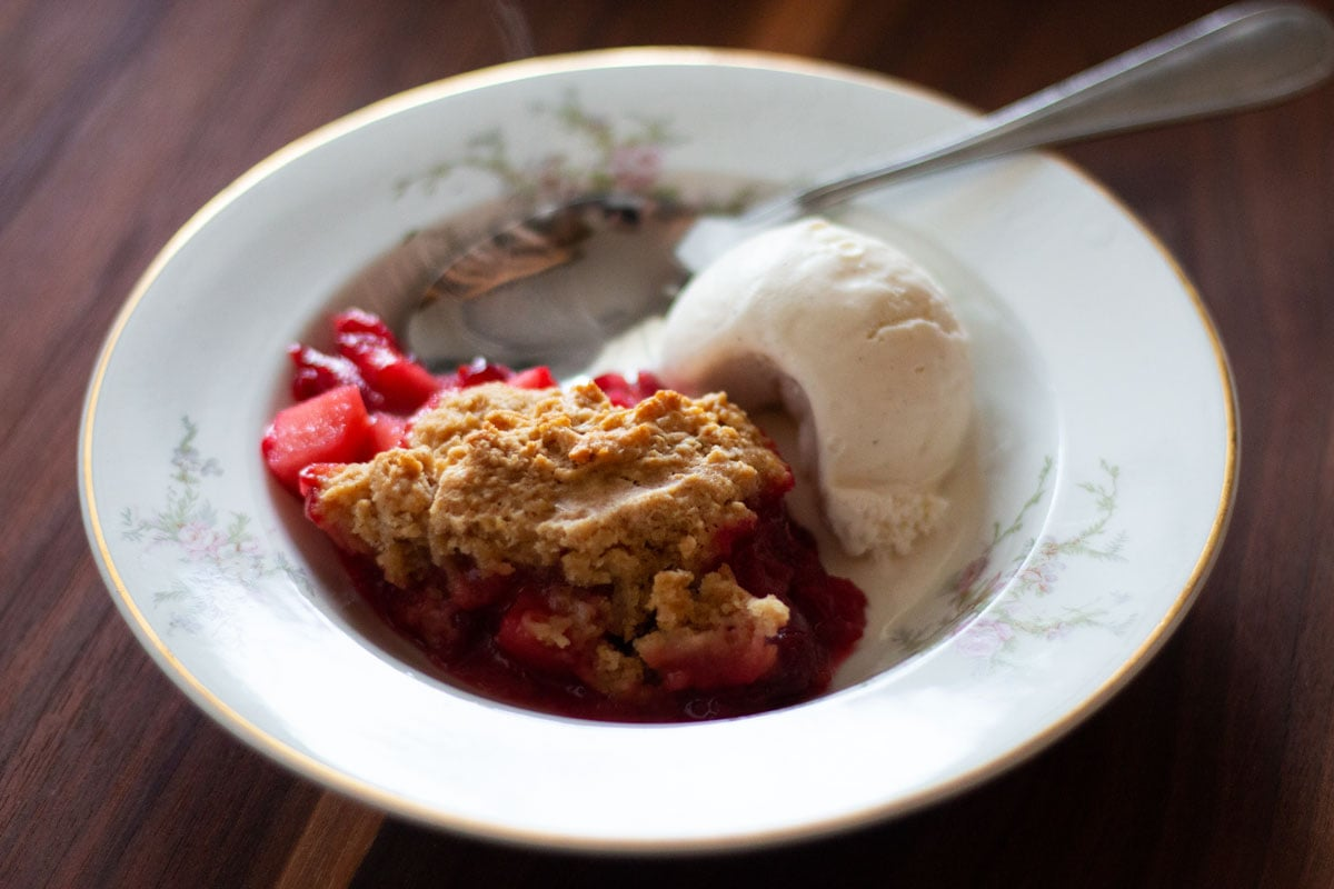 A bowl of Cranberry Apple Cobbler with Ice Cream in a antique bowl.