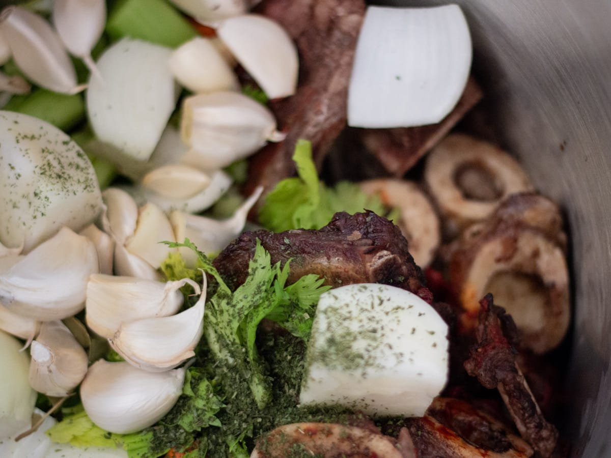 roasted beef bones and ingredients in a stock pot