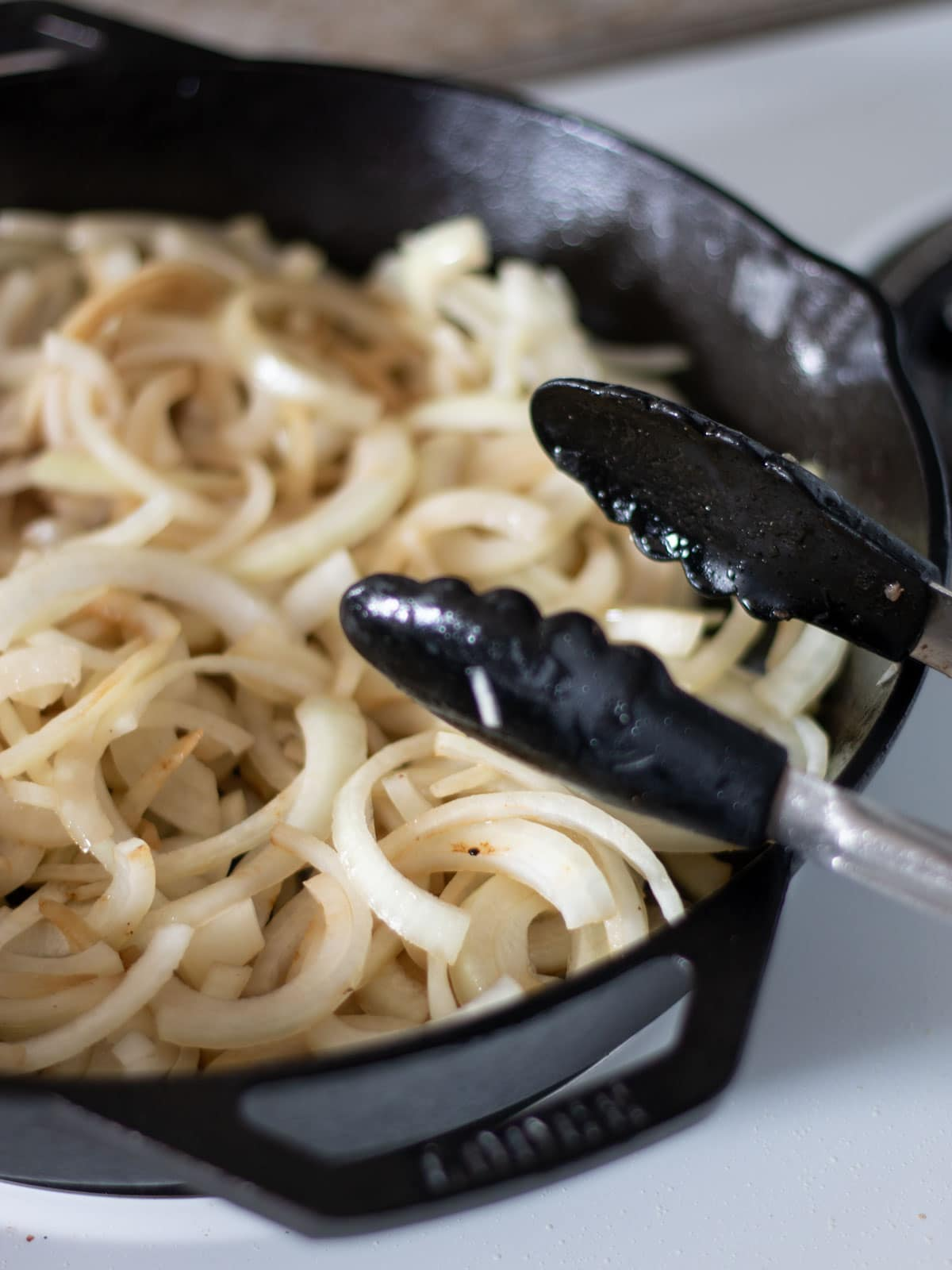 sliced onions cooking in a cast iron skillet