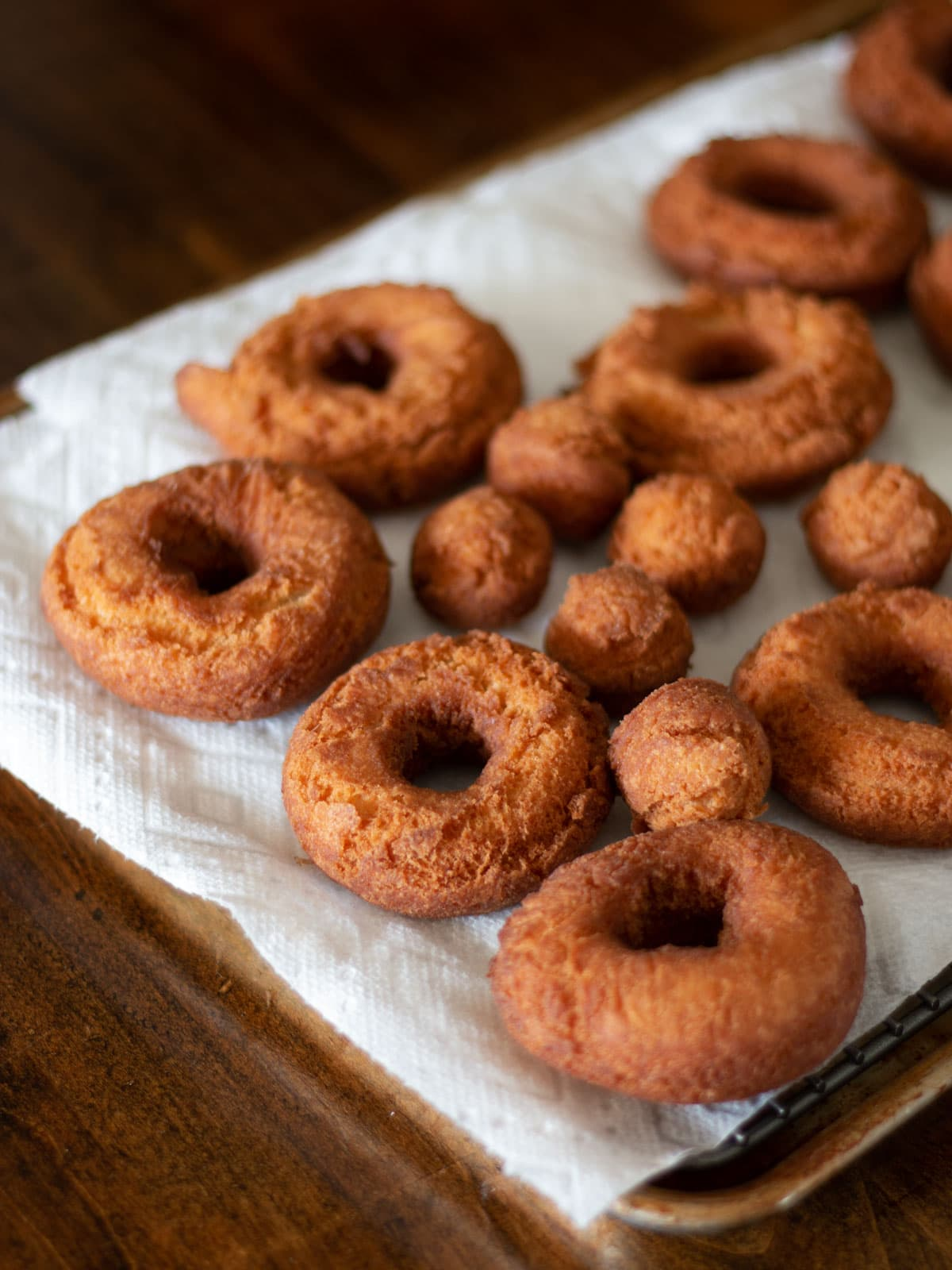 Homemade doughnuts cooling on paper towels