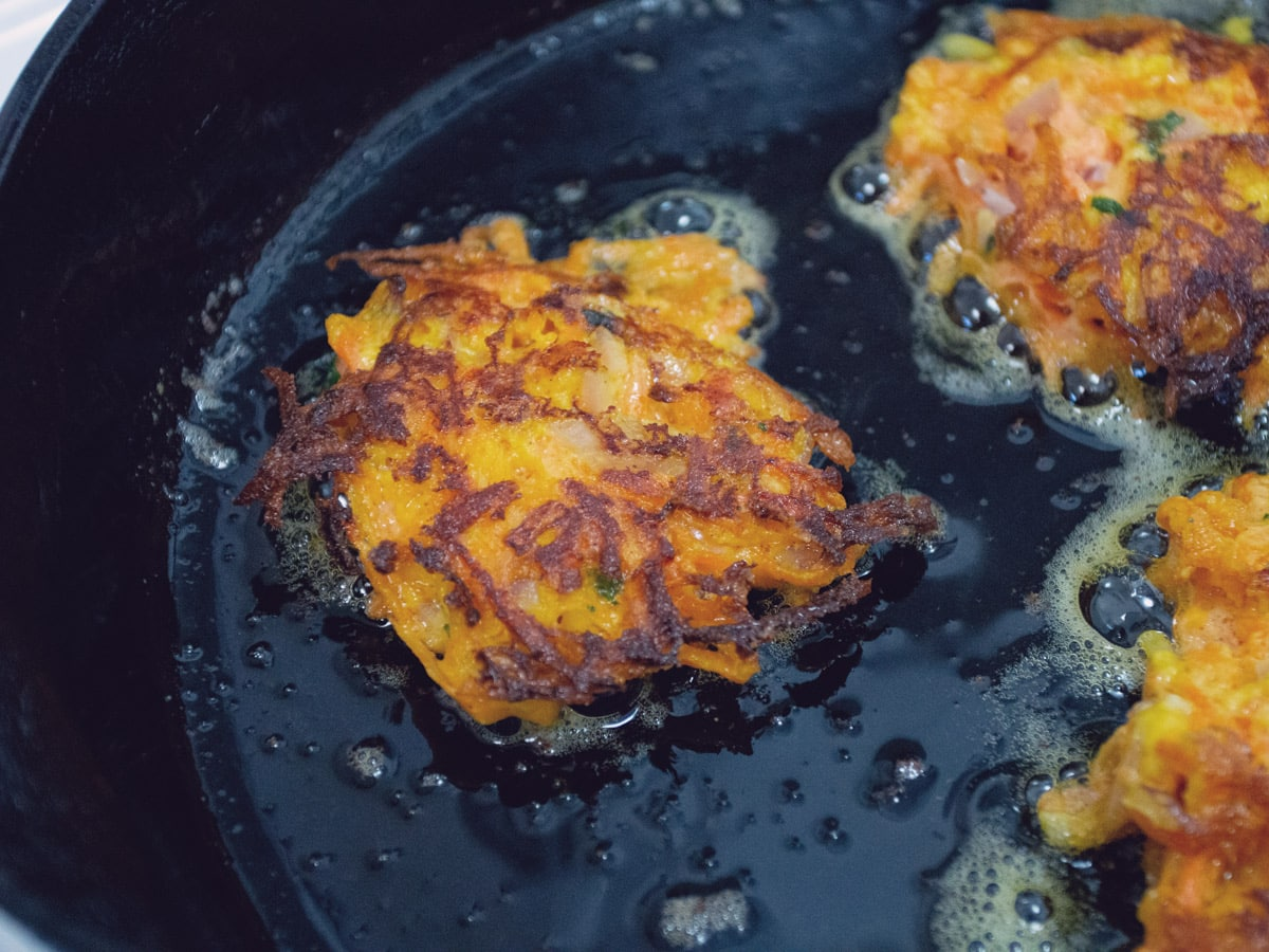 carrot fritters cooking in skillet