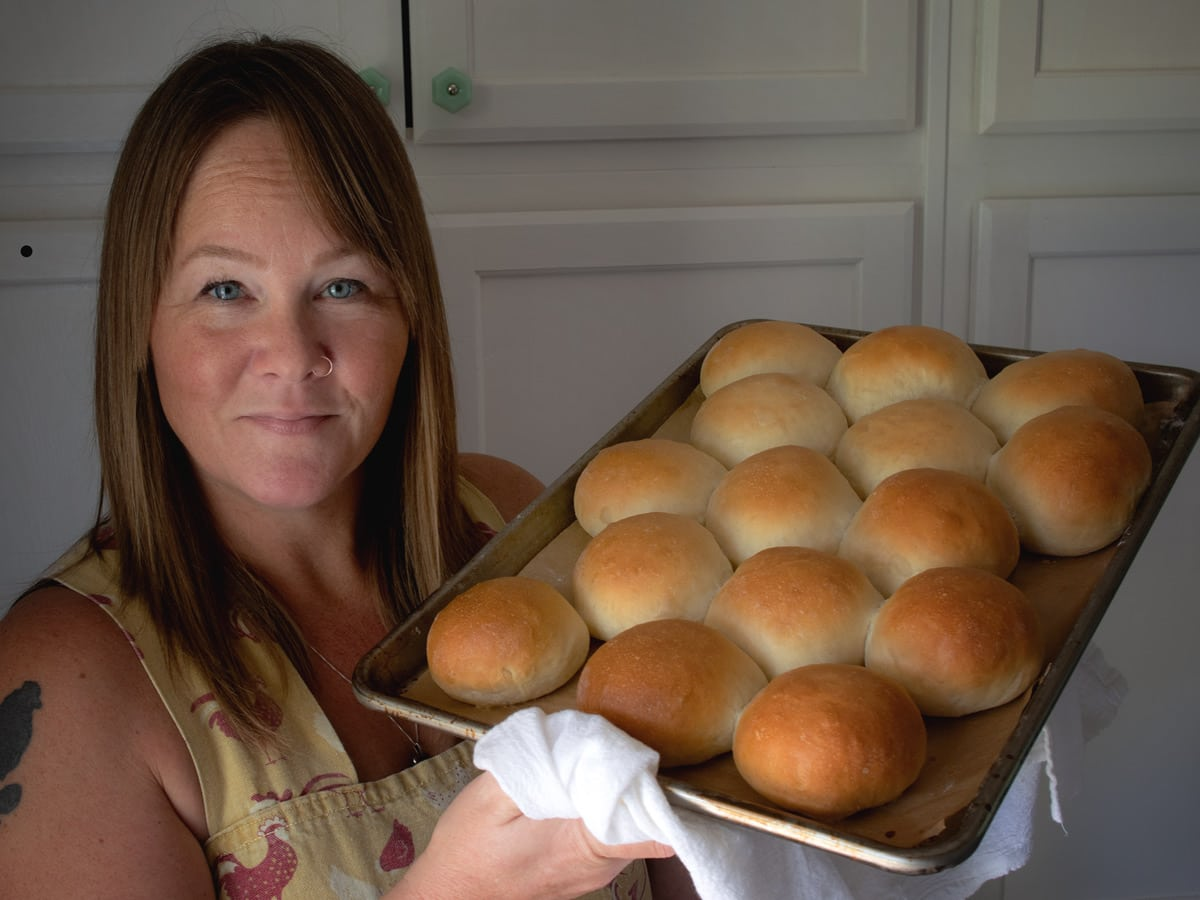 Constance holding the pan of rolls.